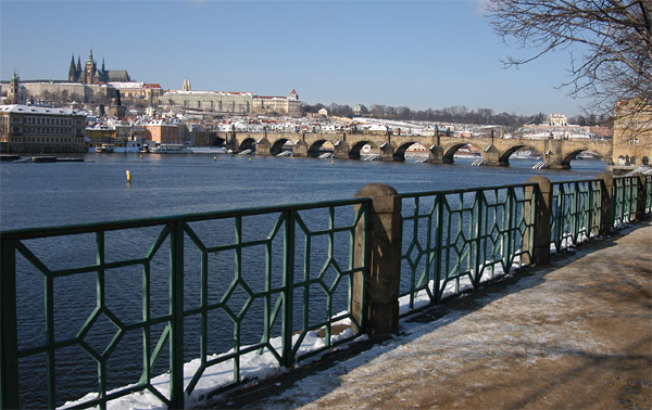 Vltava River embankment with Charles Bridge and Prague Castle in the winter with snow